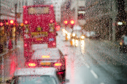 Fotografia  Rain in London view to red bus through rain-specked window