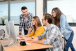 group of young cool hipster creative business people in casual wear working together in a meeting room of startup company looking at photography on computer