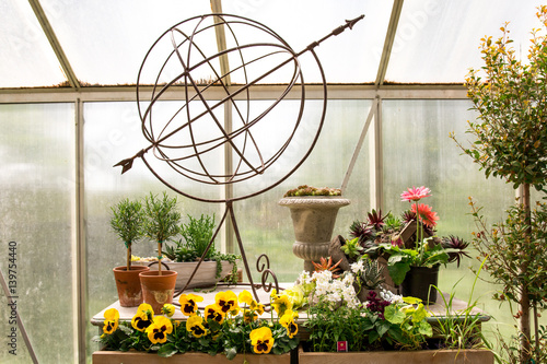 Metal sculpture of globe in greenhouse