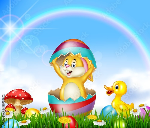 Fotografie, Tablou  Cute Easter bunny inside cracked egg with nature background