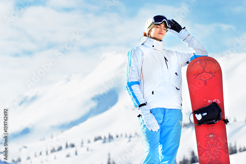 Tuinposter Wintersporten Young beautiful girl in white jacket, blue ski pants and googles on her head standing with snowboard in the snowy mountains. Winter sports.