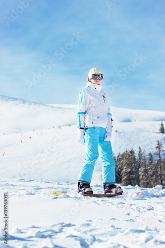 Poster Wintersporten Young beautiful girl in white jacket, blue ski pants and googles on her head riding on snowboard in the snowy mountains. Winter sports.