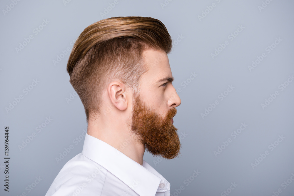 Fototapeta Side view portrait of confident bearded man with beautiful hairstyle   in white shirt looking on copy space