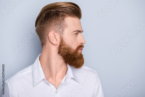 Fotobehang Kapsalon Side view portrait of confident bearded man with beautiful hairstyle in white shirt looking on copy space