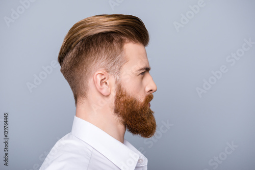Side view portrait of confident bearded man with beautiful hairstyle in white shirt looking on copy space