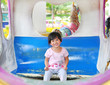 Happy adorable kid girl smiling on a carriage in a carousel