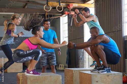 Fotografie, Obraz  Trainer motivating class doing box jumps fitness boot camp training