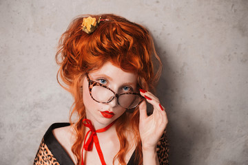 A woman with red hair in leopard print gown with glasses in hand. Red-haired girl with pale skin and blue eyes with a bright unusual appearance with a red ribbon around her neck. French courtesan