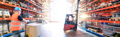 Obraz Logistik im Warenlager - Arbeiter mit Hubwagen und Gabelstapler am Hochregal // Logistics in warehouse - Worker with pallet truck and forklift truck on high rack - fototapety do salonu