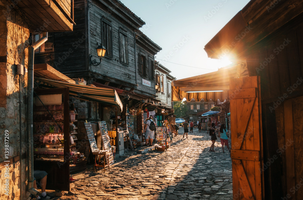 Fototapety, obrazy: People walk through pedestrian cobblestone streets of ancient Nessebar with cafe, restaurant and souvenir shops at sunset.