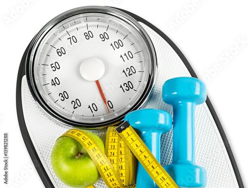 Fotografie, Obraz  measuring tape green apple dumbbell on white bathroom scale fitness concept back