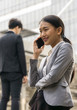 Young businesswomen, female professional in suit talking on mobile phone during work break outdoors