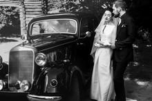 Luxury Elegant Wedding Couple Holding Hands On Background Of Stylish Black Car .  Gorgeous Bride And Handsome Groom In Retro Style. Romantic Moment. Black White Photo.