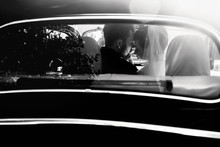 Luxury Elegant Wedding Couple Embracing In Stylish Black Car In Light. Unusual View From Back. Gorgeous Bride And Handsome Groom In Retro Style. Black White Photo