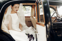 Gorgeous Elegant Bride Posing In Stylish Retro Black Car, Sitting Inside In Saloon Holding Bouquet Of Callas. Luxury Wedding In Vintage Style. Unusual Gown And Veil