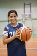Girl standing with ball in basketball court