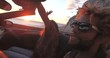 Handsome black man partying with friends while driving in convertible