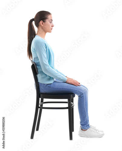 Posture concept. Young woman sitting on chair against white background Wall mural