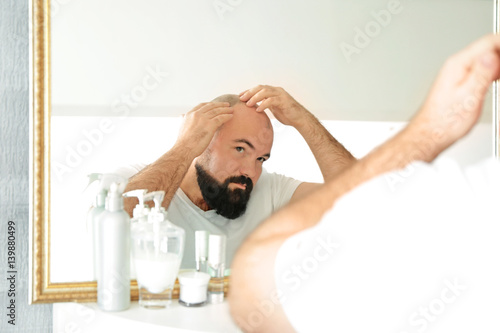 Adult man with hair loss problem looking in mirror at home Tapéta, Fotótapéta