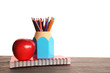 Colorful pencils in holder, red apple and exercise book on wooden table against white background