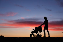 Silhouette Mother Pulling Baby Stroller Against Beach Sunset.