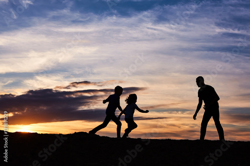 Fototapeta Father and children on the beach at the sunset time. Concept of friendly family. obraz na płótnie