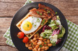 Breakfast with fried egg, waffles, bacon, mix lettuce and beans close-up. horizontal top view