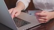 Hands holding plastic credit card and using laptop. Online shopping
