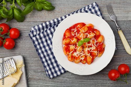 Fotografia Serving gnocchi in tomato sauce with cheese.