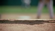 Rack focus from infield players to close-up of baseball cleats pawing dirt