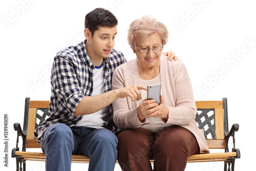 Fotografie, Obraz  Young man showing elderly woman how to use mobile phone