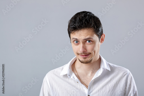 Fototapety, obrazy: handsome young frustrated and resentful man in white shirt on gr