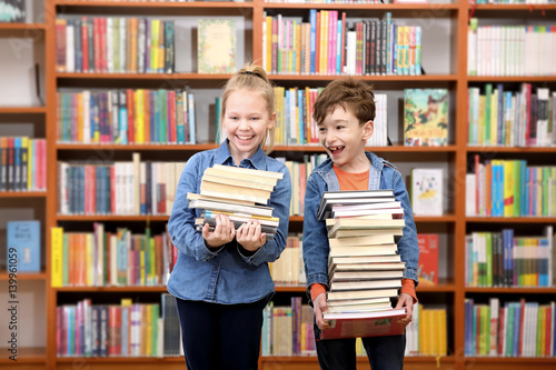 Fotografie, Obraz  Cute boy and girl  reading book in library