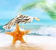 Starfish on sandy beach and umbrella