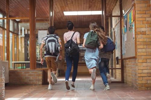 Plakat Podekscytowani koledzy z klasy biegają w korytarzu