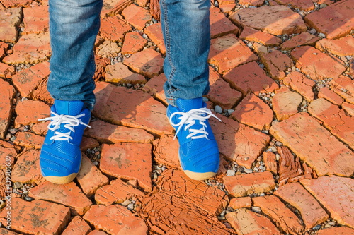 A teenager in jeans and  blue Adidas sneakers stands on a  path. Wallpaper Mural