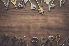 Many Different Keys On Brown Wooden Background With Copy Space In The Centre