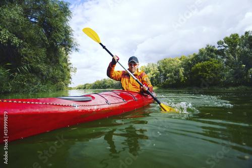 Obraz na plátně  A trip by the river on a kayak.
