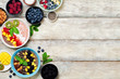 Variation of healthy smoothie breakfast bowls with berries, fruits and nuts.