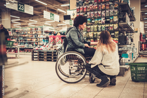 Photo  Young girl helping her disabled mothter in wheelchair in a department store