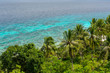 Elevated island view over palm trees and coastal jungle out to a shallow and calm turquoise tropical sea on a sunny day.
