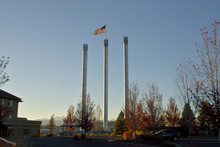 Smokestacks And American Flag At Bend Old Mill District; Bend, Oregon