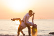 Young couple dancing on seaside at golden sunrise
