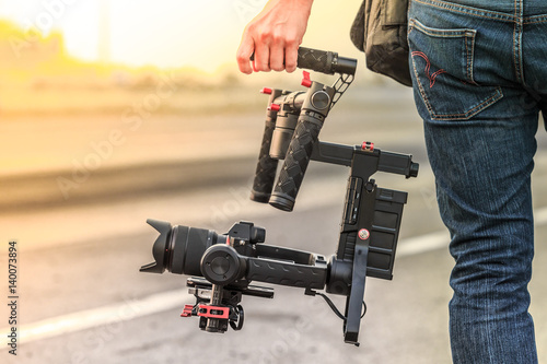 Obraz Videographer with gimbal video camera dslr, Professional video equipment, Videographer in event film production shoot video. - fototapety do salonu