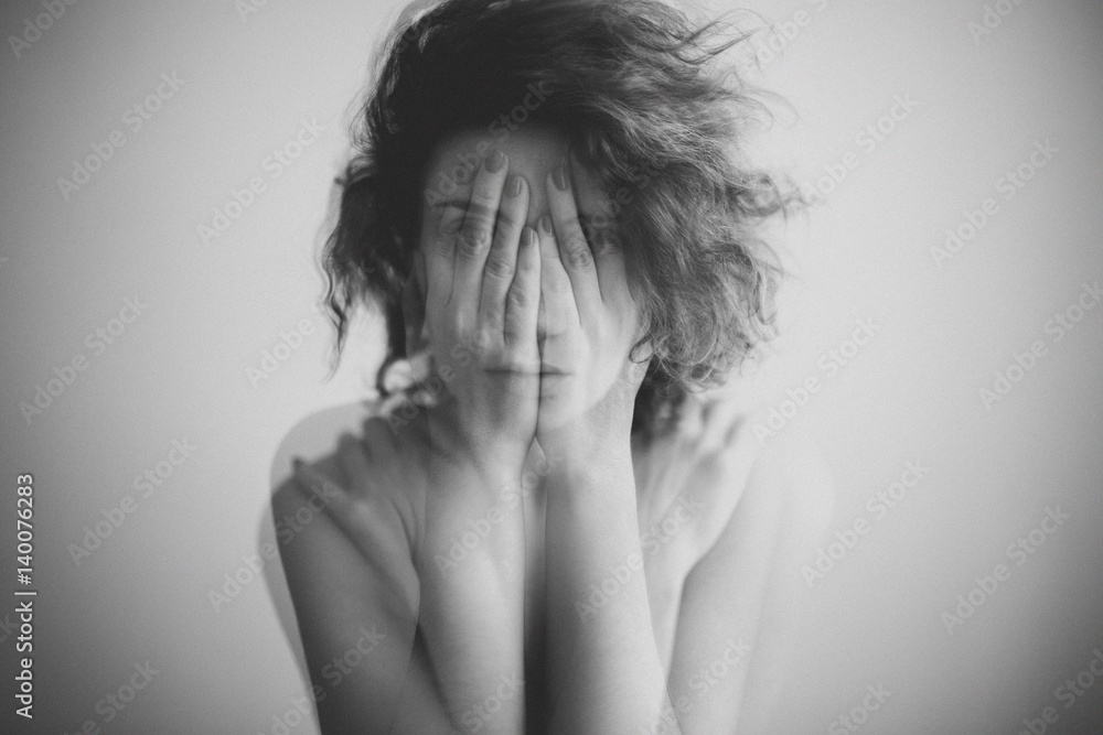 Fototapeta Double exposure black and white portrait of a woman covering her face and eyes with her hands