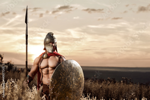 Strong Spartan warrior in battle dress with a shield and a spear Fototapete