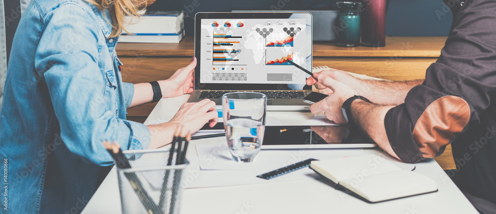 Fototapety, obrazy: Businessman and businesswoman sitting at table in front of laptop and working. Graphs,charts and diagrams on PC screen.