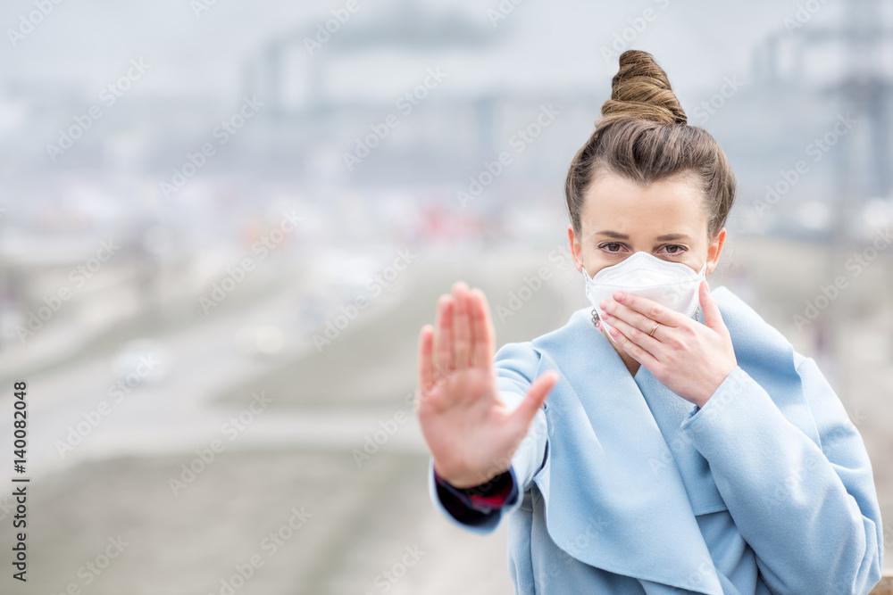 Młoda kobieta w masce ochronnej czuje się źle w mieście z zanieczyszczeniem powietrza od ruchu i produkcji. Koncepcja smogu