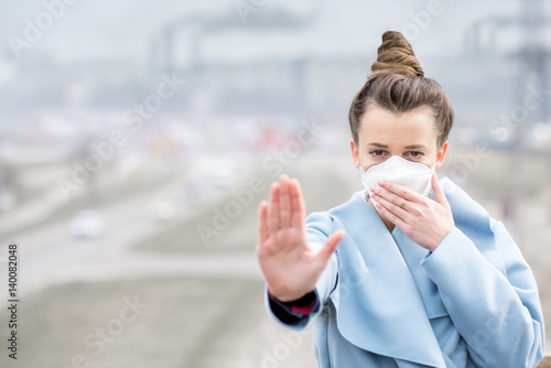 Young woman in protective mask feeling bad in the city with air pollution from traffic and manufacturing Poster