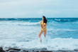 Pretty girl in sexi yellow swimsuit standing on rock